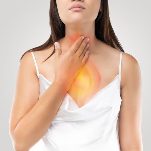 Kobieta dotyka przełyku. Przyczyny zgagi - kiedy zgłosić się do lekarza