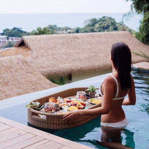 Kobieta w basenie ze śniadaniem na tacy. Wakacyjna dieta - co zrobić, by nie przybrać na wadze