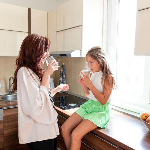 Mama z córką piją wodę w kuchni. Nawodnienie organizmu - jak o nie zadbać każdego dnia