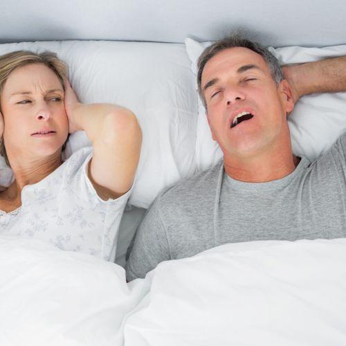 Kobieta zatyka uszy, gdy mężczyzna chrapie. Skutki bezdechu sennego - jak bardzo mogą być groźne
