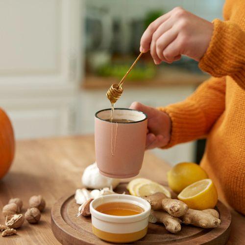 Kobieta przygotowuje rozgrzewającą herbatę. Jak dbać o zdrowie jesienią i wzmocnić układ odpornościowy.