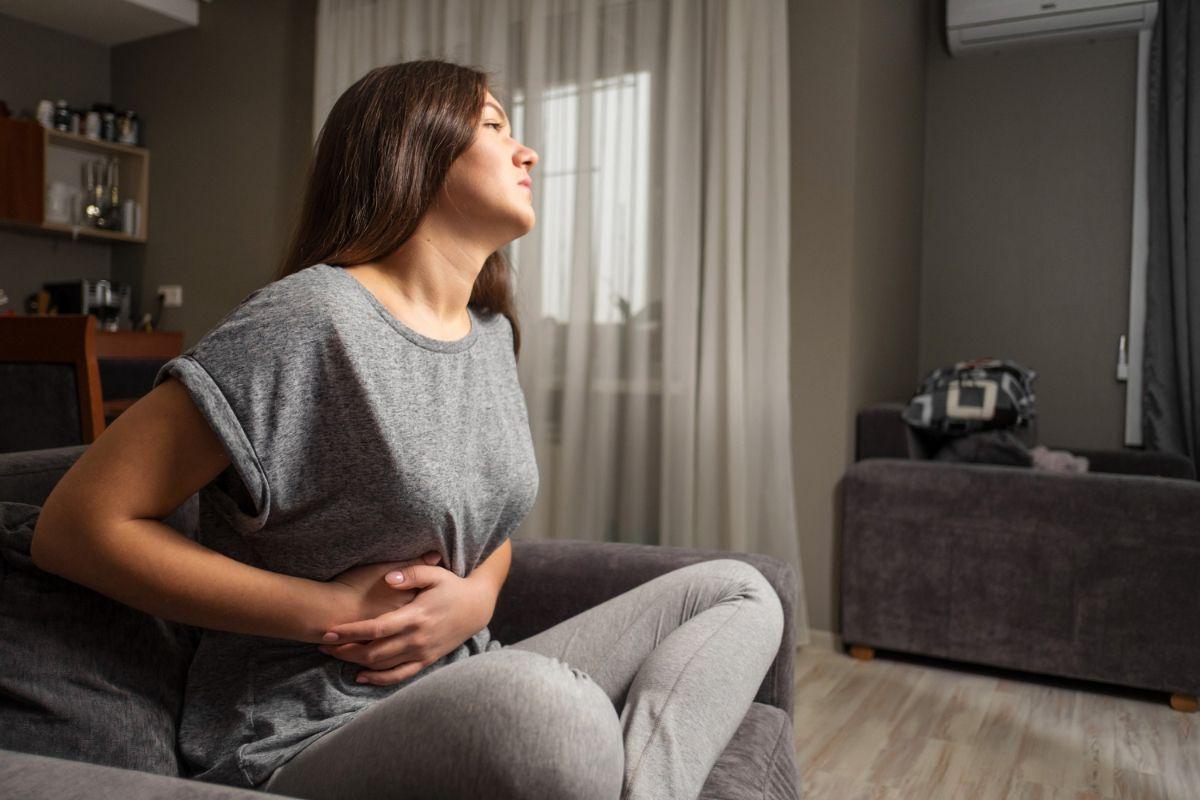 Kobieta trzymająca się z bok brzucha. Przewlekłe zapalenie pęcherzyka żółciowego