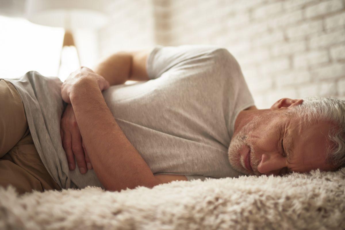 Mężczyzna z bolącym brzuchem na łóżku. Kamica żółciowa - jak ją rozpoznać i kiedy zgłosić się do lekarza