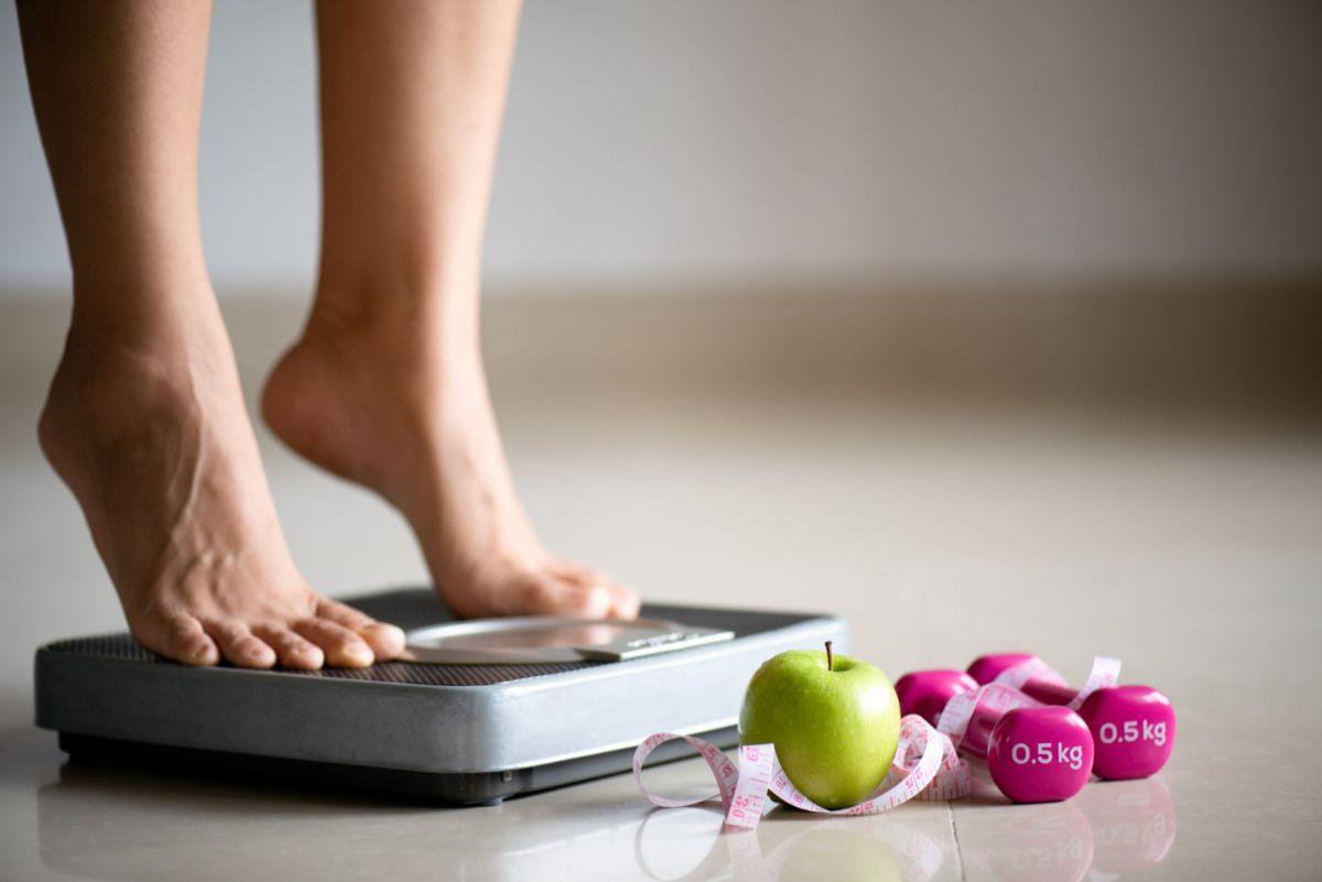 Kobieta stoi na wadze. Zależność: dieta względem nadwagi